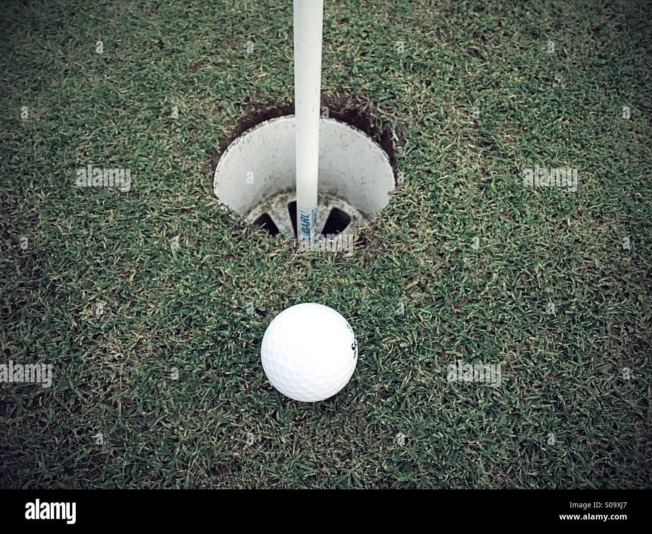 Pelota de golf cerca al agujero Imagen De Stock