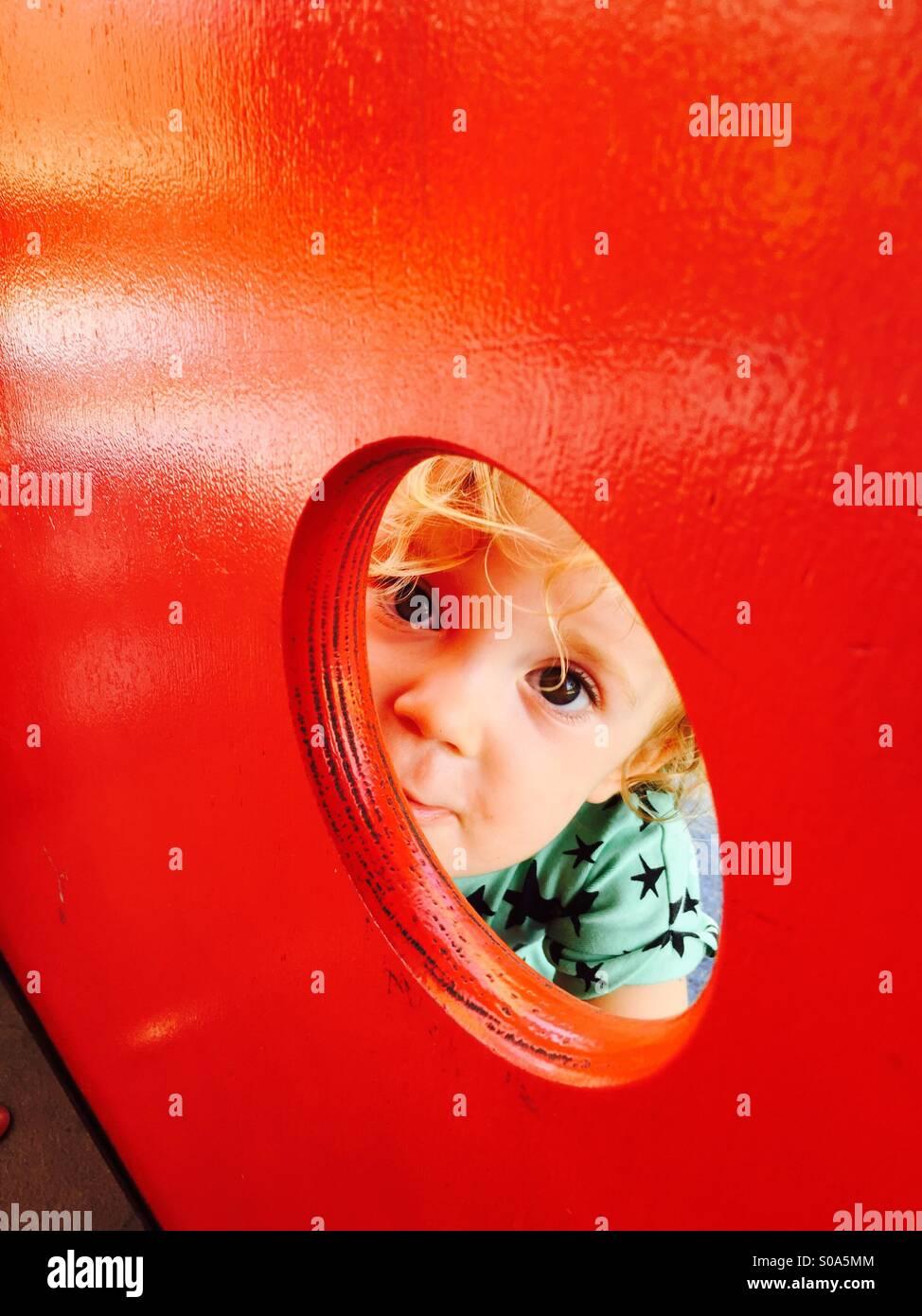 Hola poco impertinente niña! Tener un juego y una sonrisa con su peekaboo maneras. Imagen De Stock