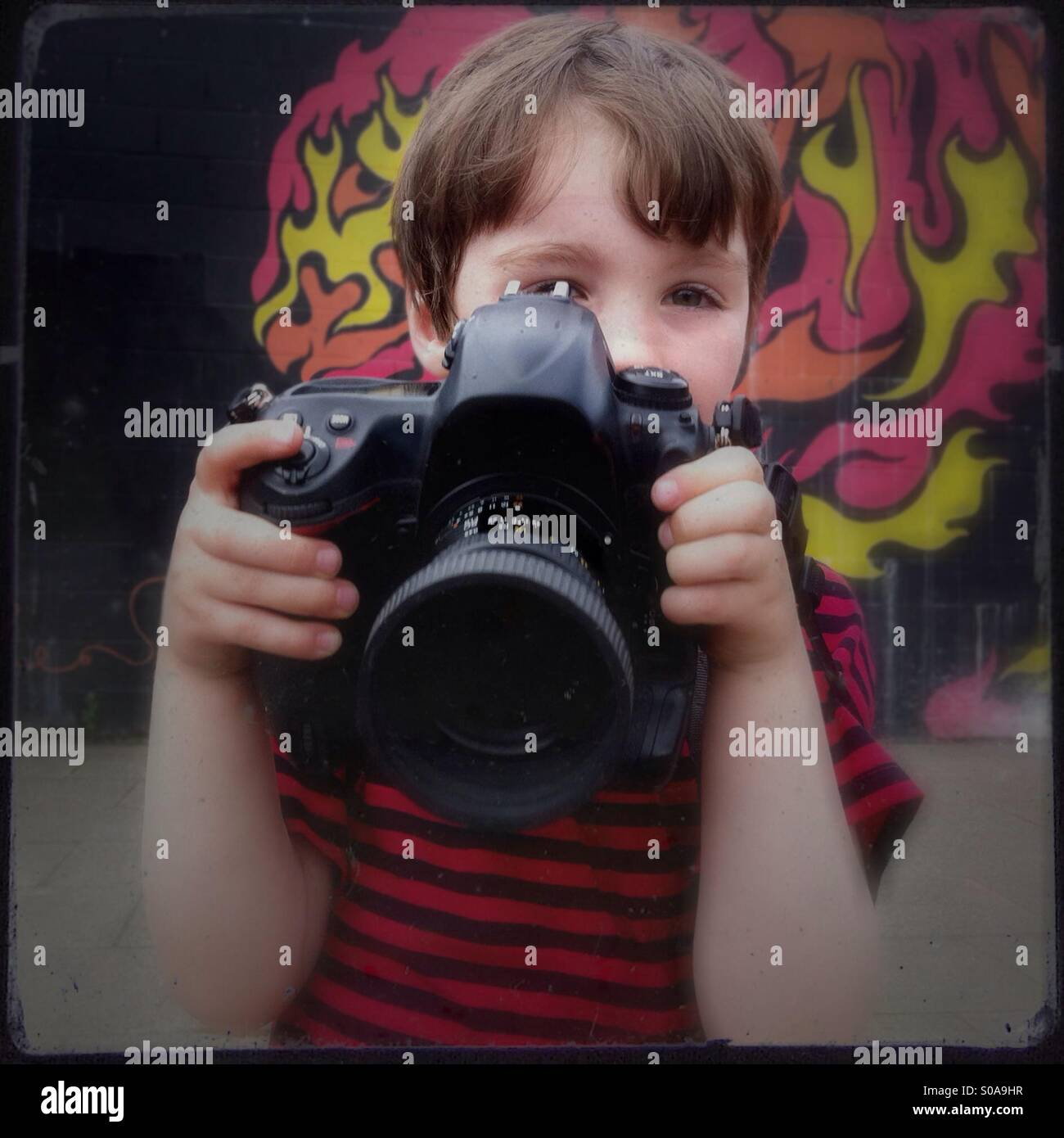 Niño pequeño con una gran cámara. Un niño de cinco años con una slr de tamaño completo. Imagen De Stock