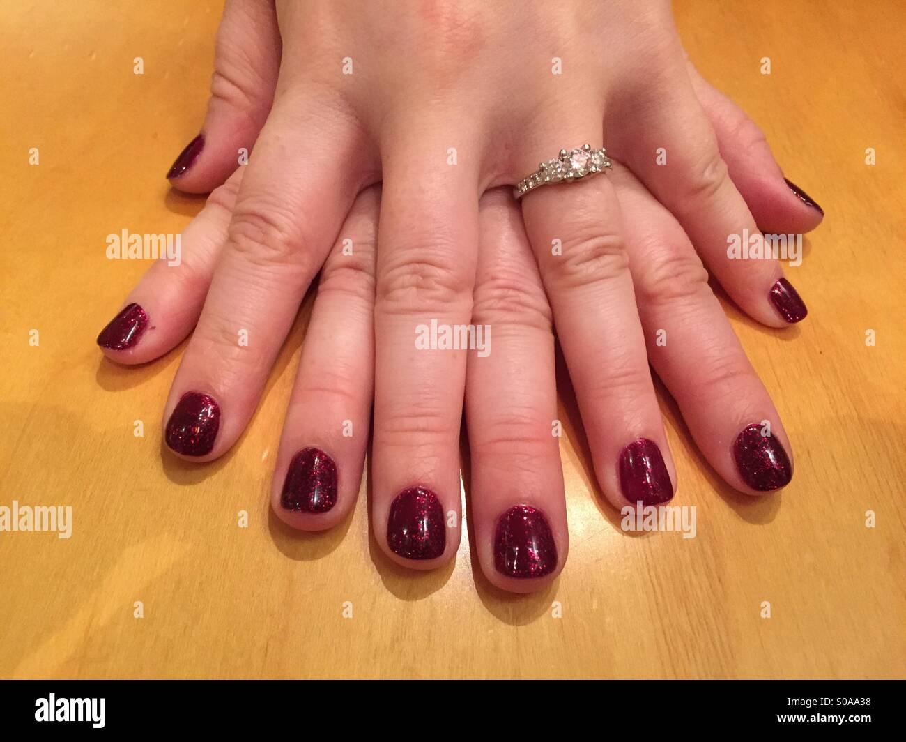 Las dos manos de forma plana sobre la mesa con los dedos entrelazados y con uñas pintadas y un anillo de compromiso. Imagen De Stock