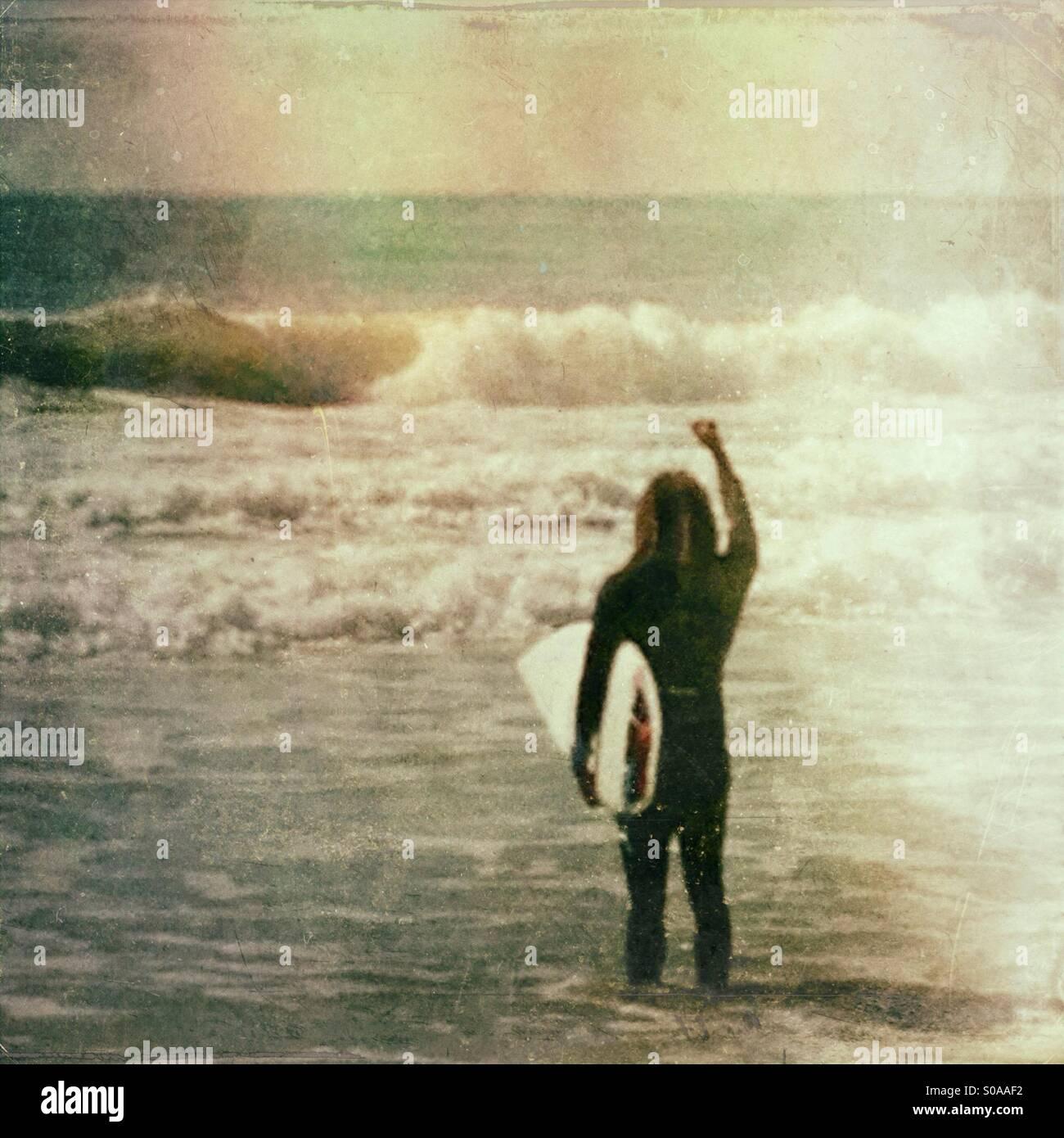 Emocionada surfer mirando las olas. Foto de stock
