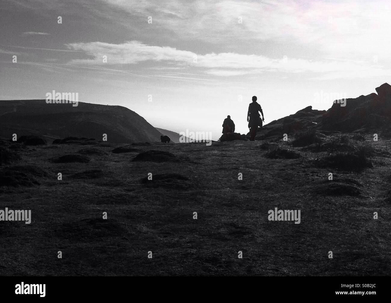 Siluetas de un padre, su hijo adolescente y su perro caminando hacia el borde del acantilado para ver vistas impresionantes Imagen De Stock