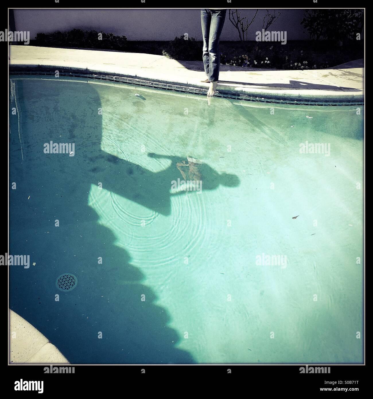 Una sombra en el fondo de una piscina de buceo de una persona fuera de un trampolín. Foto de stock