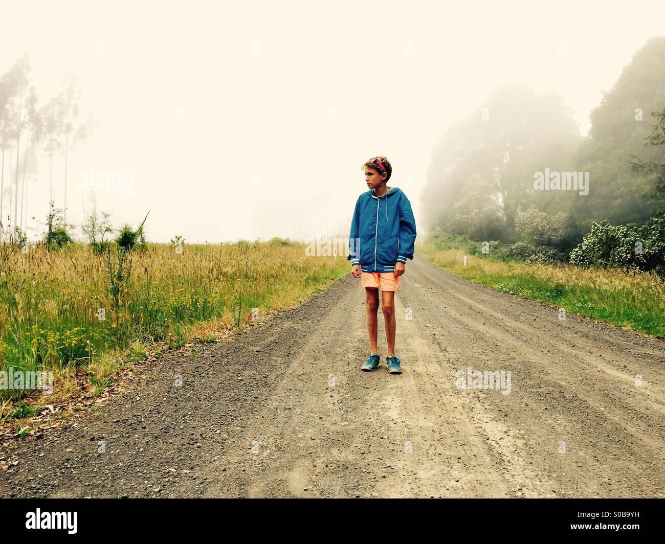 Un muchacho de 11 años caminando por la vía de un país en un día brumoso Foto de stock