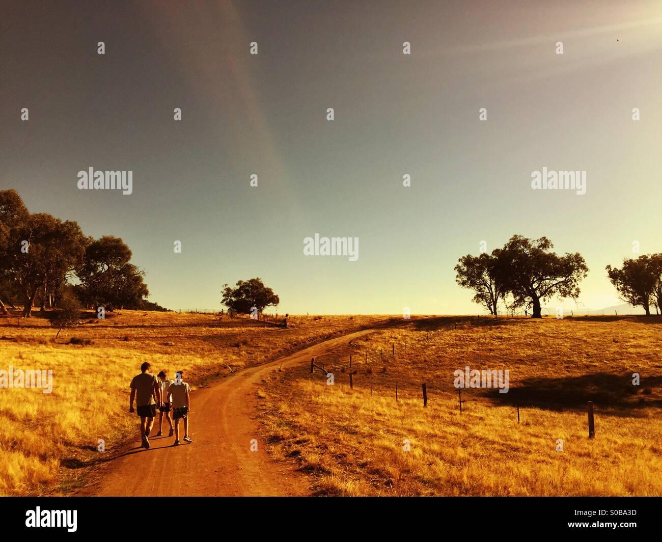 Un padre y sus dos hijos caminar a lo largo de una pista en el país en Australia Foto de stock