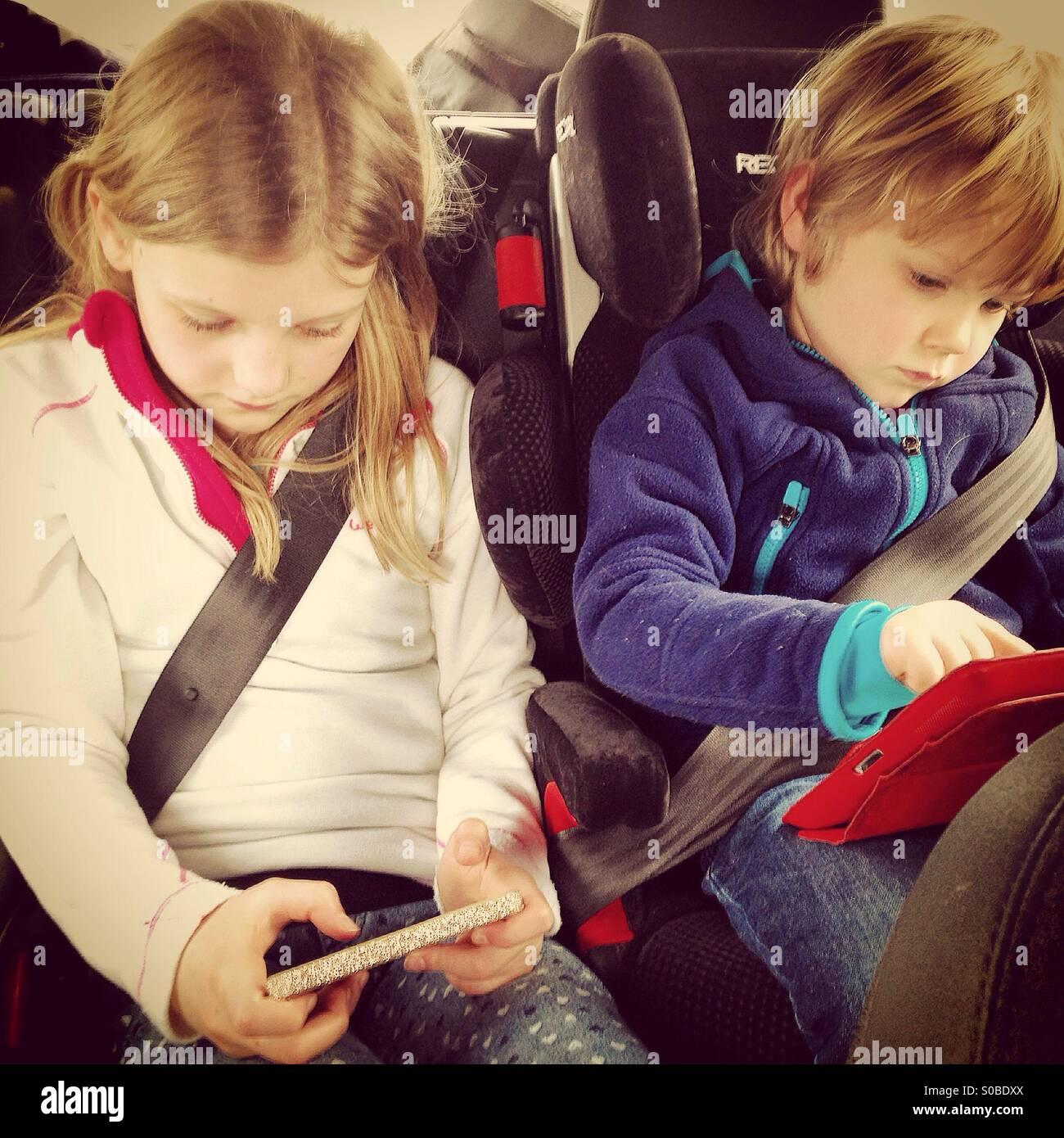 Niños jugando en las pantallas en un coche Imagen De Stock