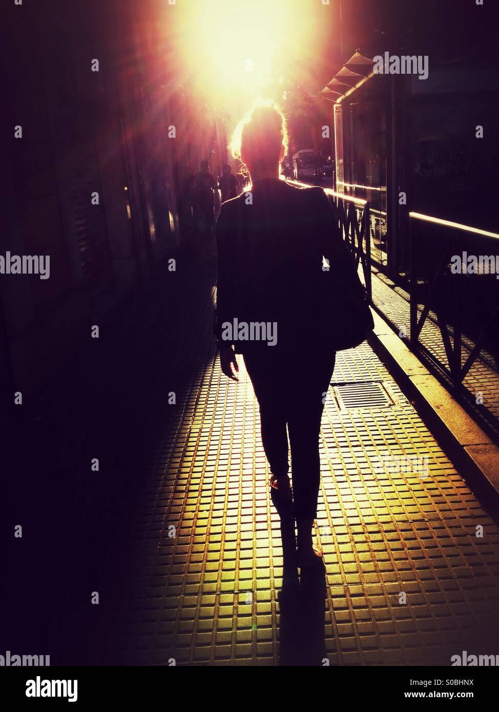 Vista posterior de la mujer caminando calle abajo en el sol Imagen De Stock
