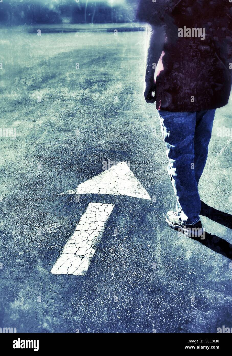 Hombre de pie junto a una pintada de flecha hacia arriba o hacia adelante Foto de stock