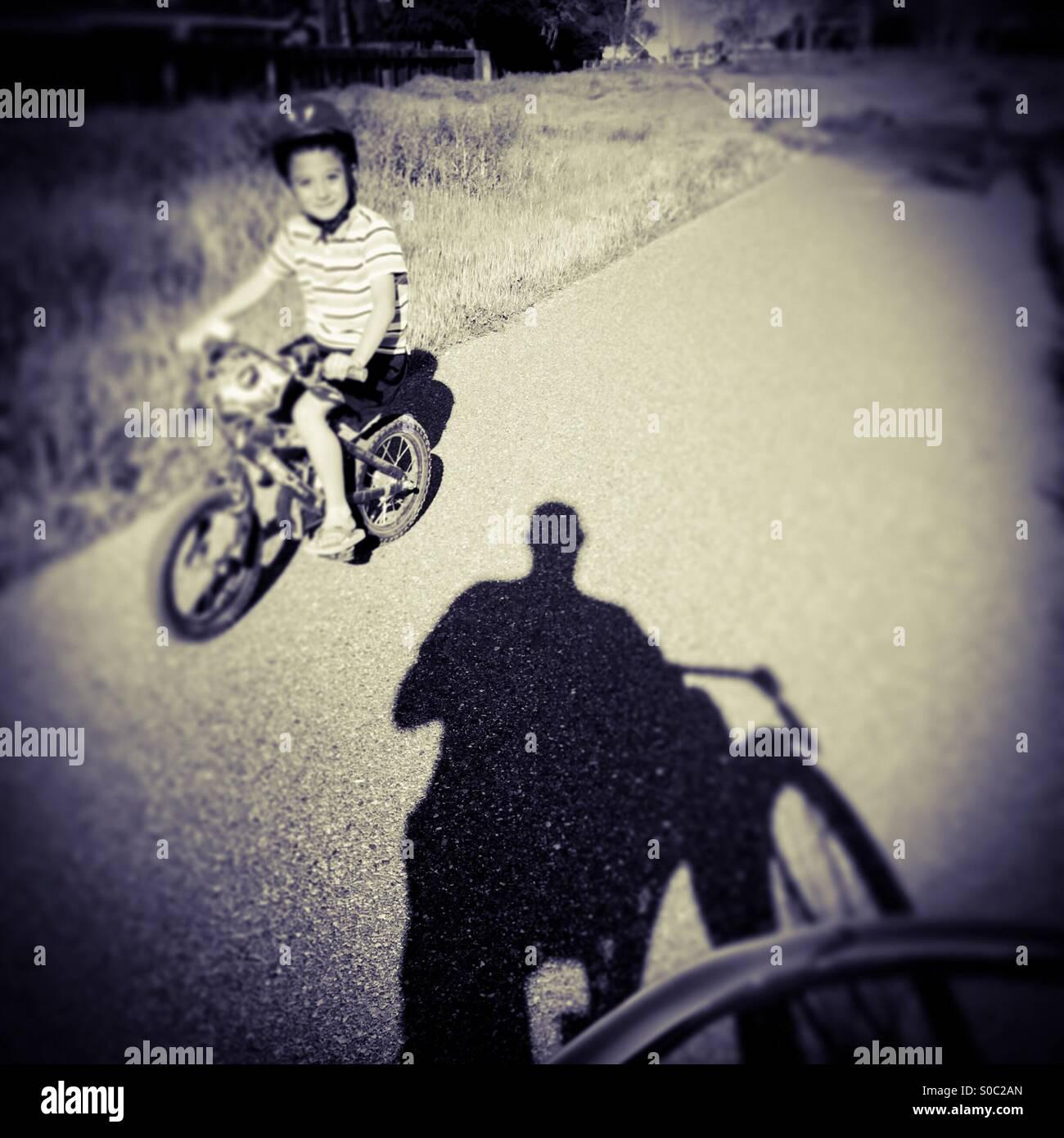 Un niño de siete años monta su bicicleta por un hombre en una bicicleta de ruta. Imagen De Stock