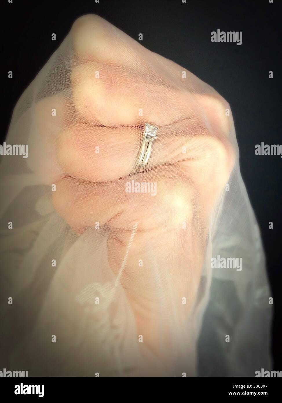 Un puño apretado usando un anillo de bodas, y agarrando pura gauzy tejido. Imagen De Stock