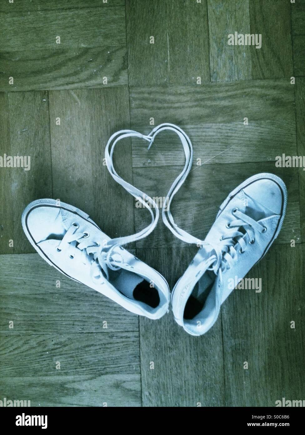 En forma de corazón blanco cordones con instructores sobre un piso de madera. Imagen De Stock