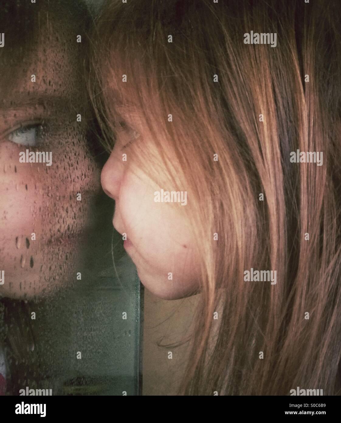 Chica presionando su nariz contra el espejo del baño mojado Imagen De Stock