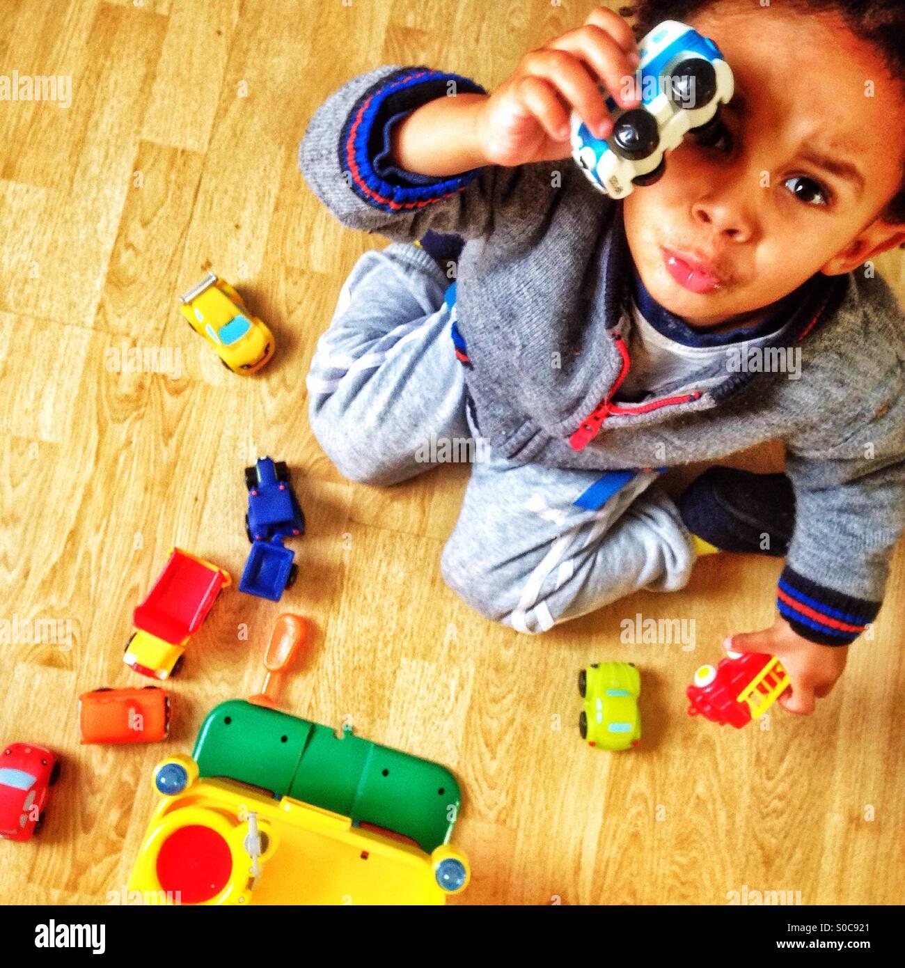 Niño jugando con sus juguetes. Imagen De Stock
