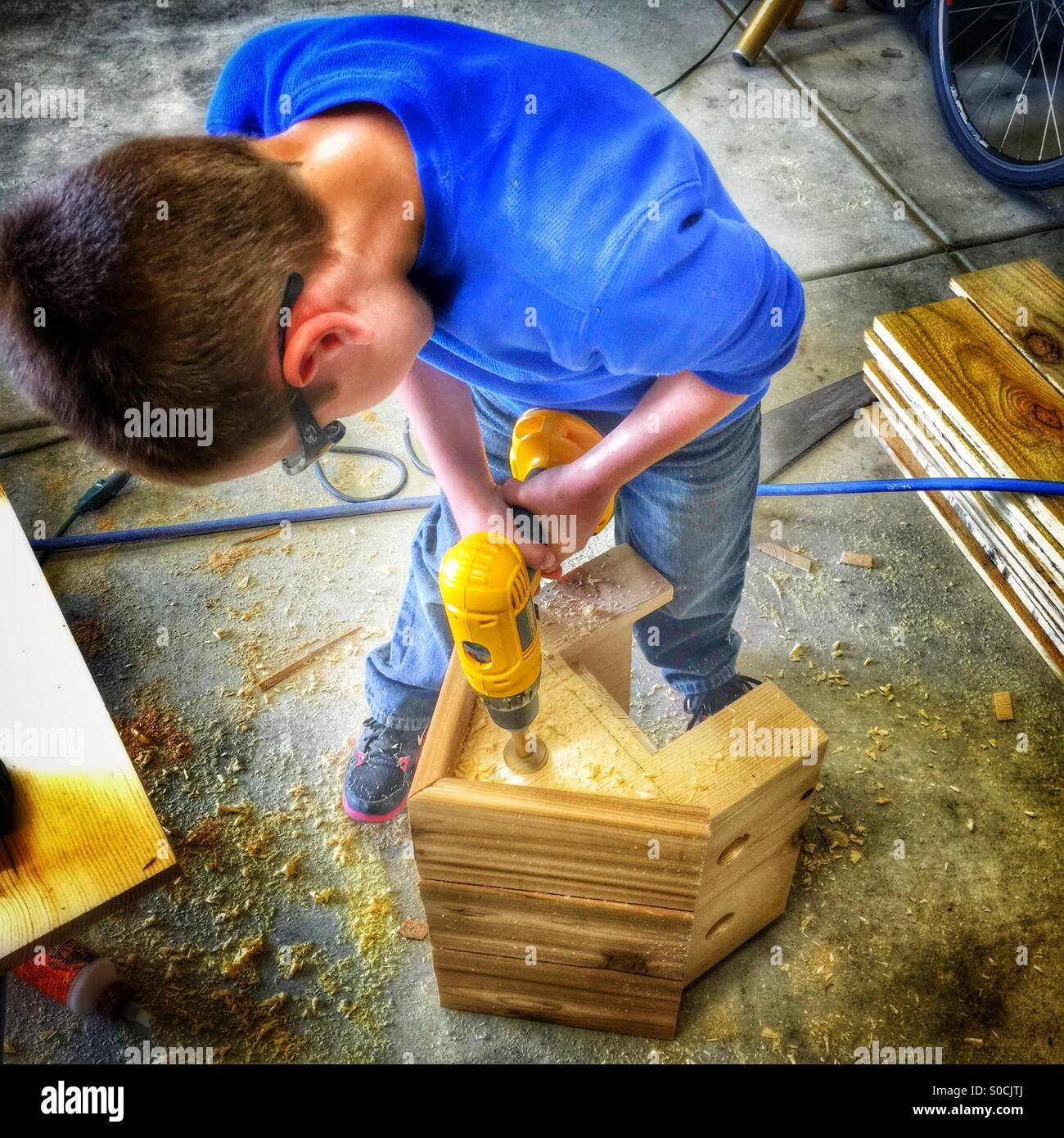 Joven taladra un orificio en una casita para aves de madera Imagen De Stock