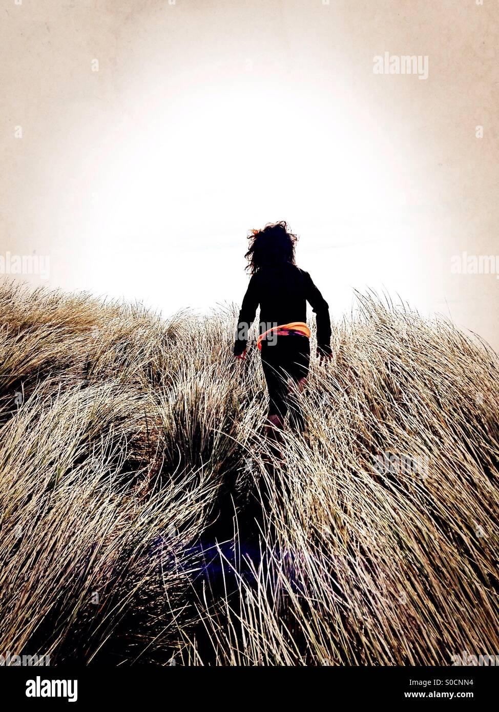 Una niña caminando en el pasto alto. Imagen De Stock