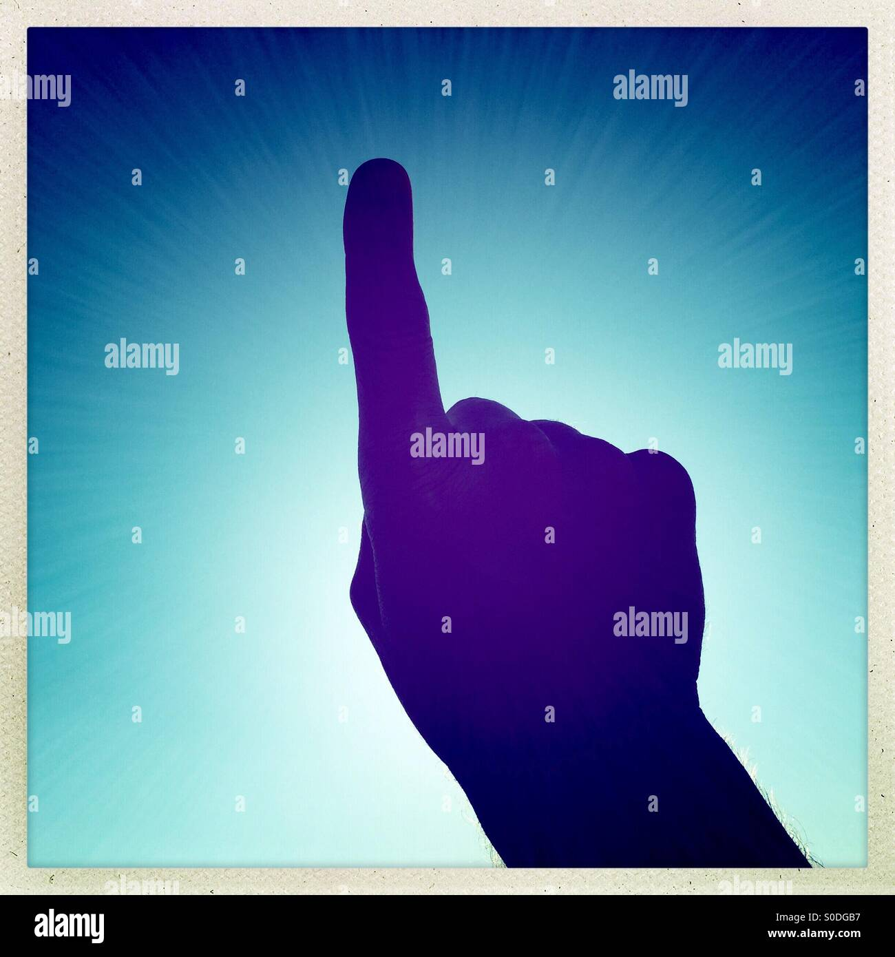 Un dedo levantado contra el cielo azul Imagen De Stock