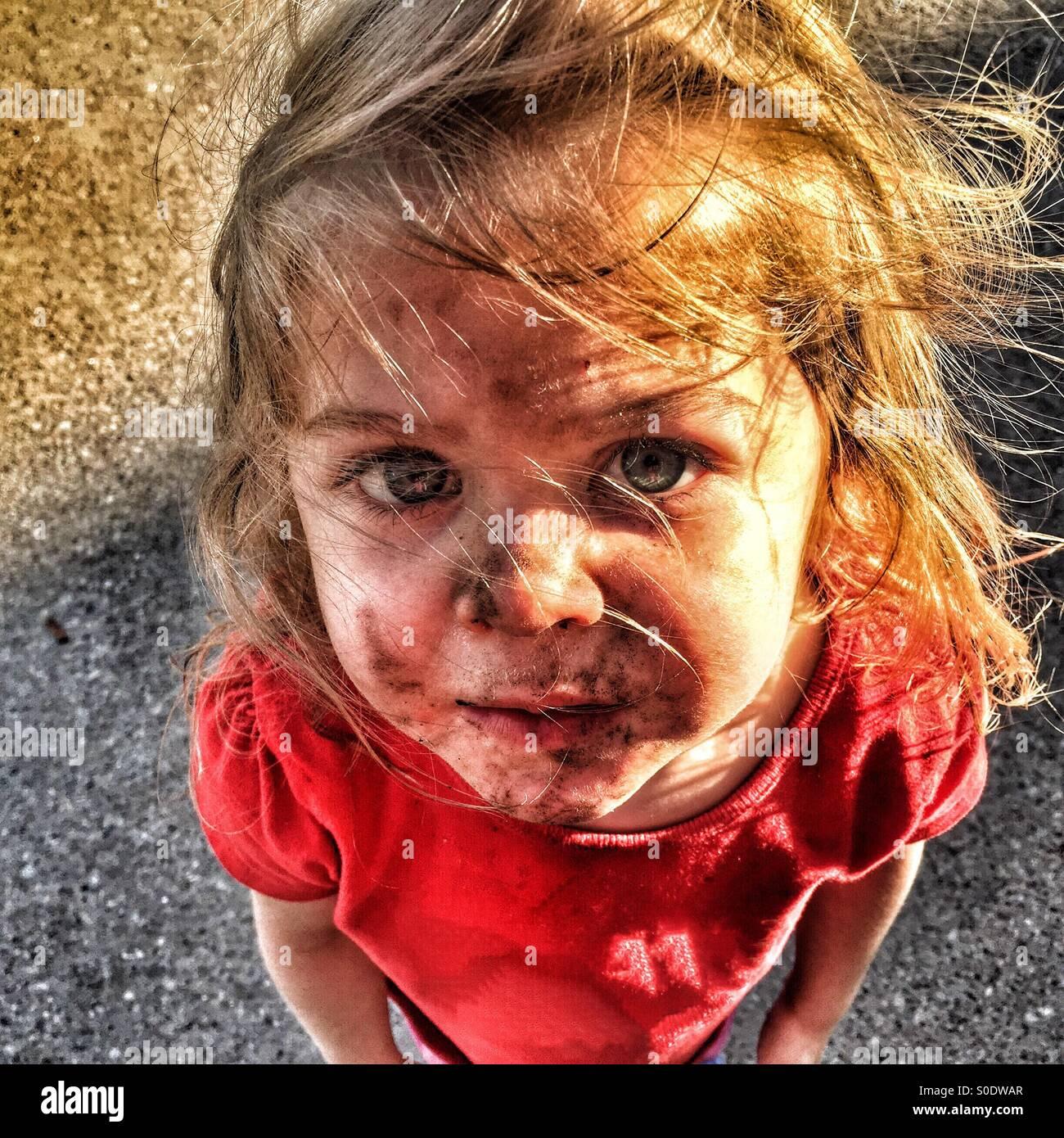 Niño con una cara sucia y el cabello alborotado mirando hacia arriba Imagen De Stock