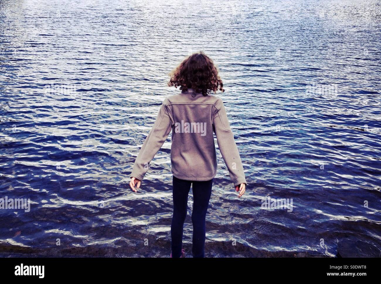 Niña mirando a lo largo de lago con sus brazos extendidos Imagen De Stock