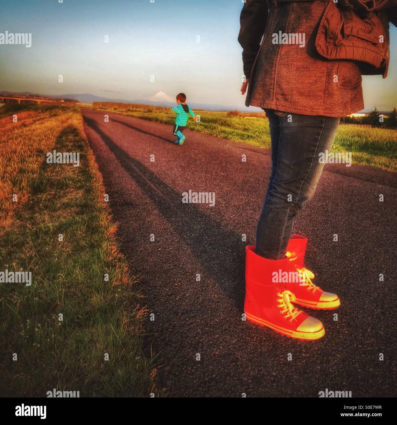 Una mamá usando botas rojas relojes mientras su niño huye de la ruta en la tarde. Imagen De Stock