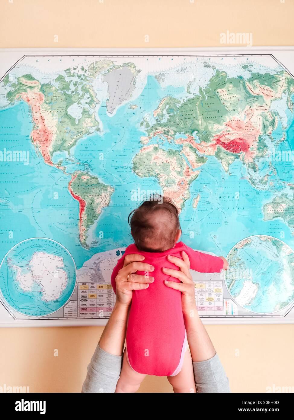 ¡Hola, mundo! Padre sosteniendo a su bebé chica enfrente mapa del mundo Imagen De Stock