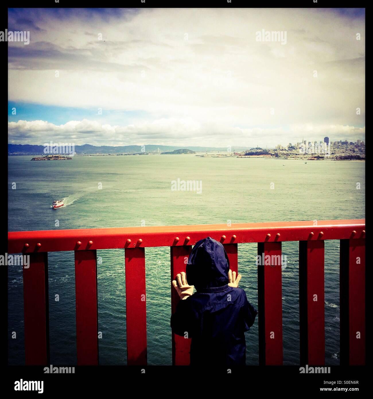 Un niño de siete años mira a un barco de cruceros turísticos y San Francisco a través de la Imagen De Stock
