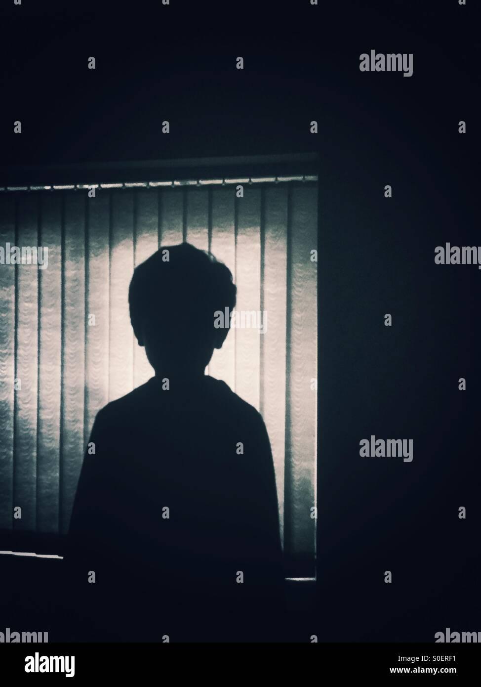 Silueta de un niño por la ventana Imagen De Stock