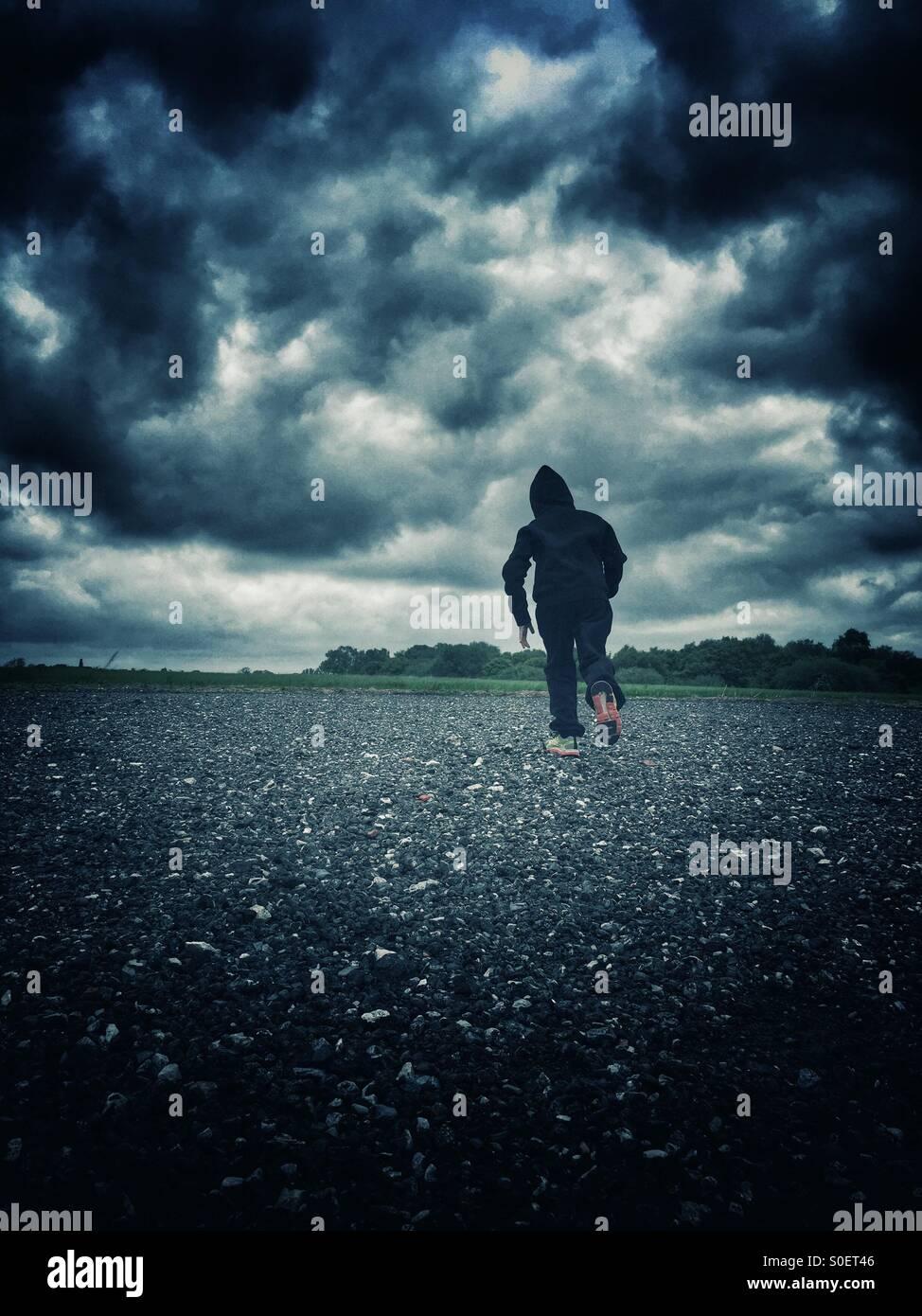 Niño encapuchado alejarse corriendo Imagen De Stock