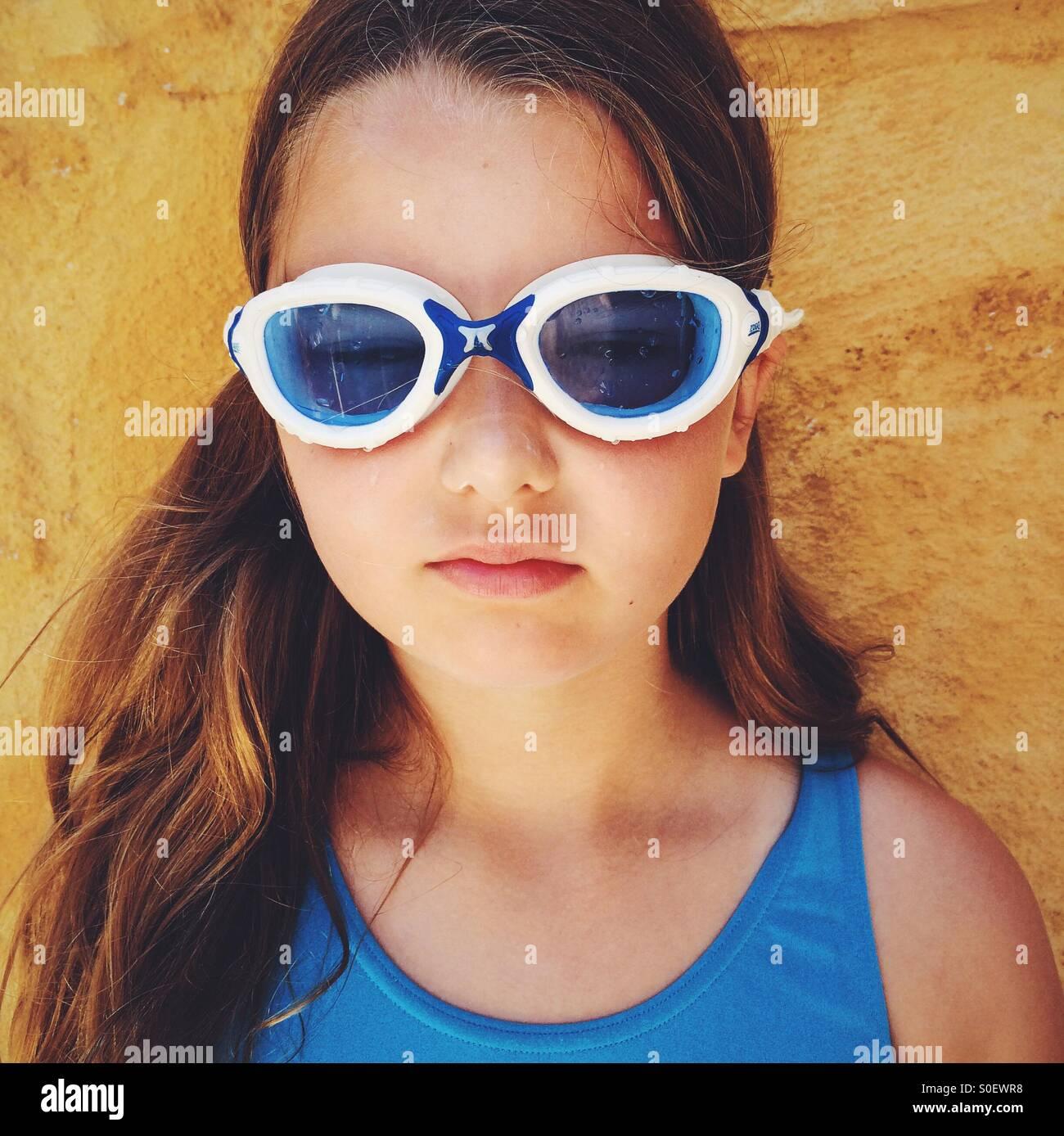Niña, vestida con gafas de natación y un bañador azul. Imagen De Stock