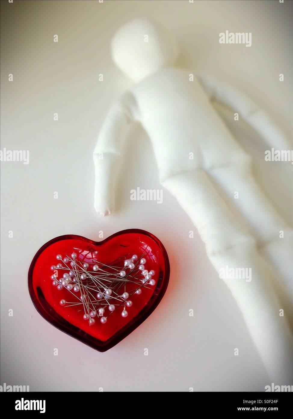 Pasadores en un plato en forma de corazón junto a un muñeco vudú en blanco. Imagen De Stock