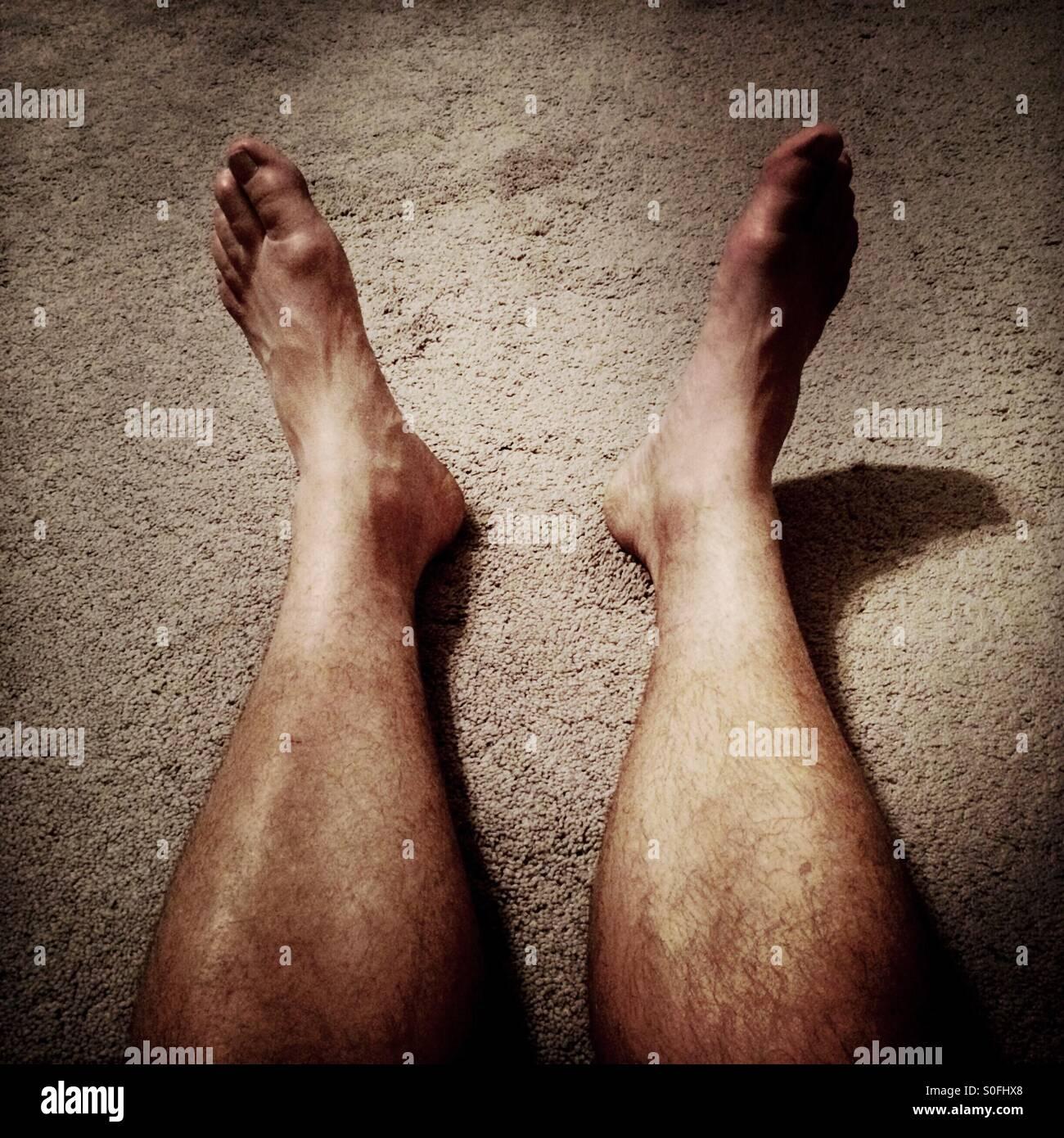 Un hombre de piernas peludas en alfombras de pelo largo. Imagen De Stock