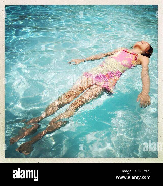 Chica flotando en la piscina Imagen De Stock
