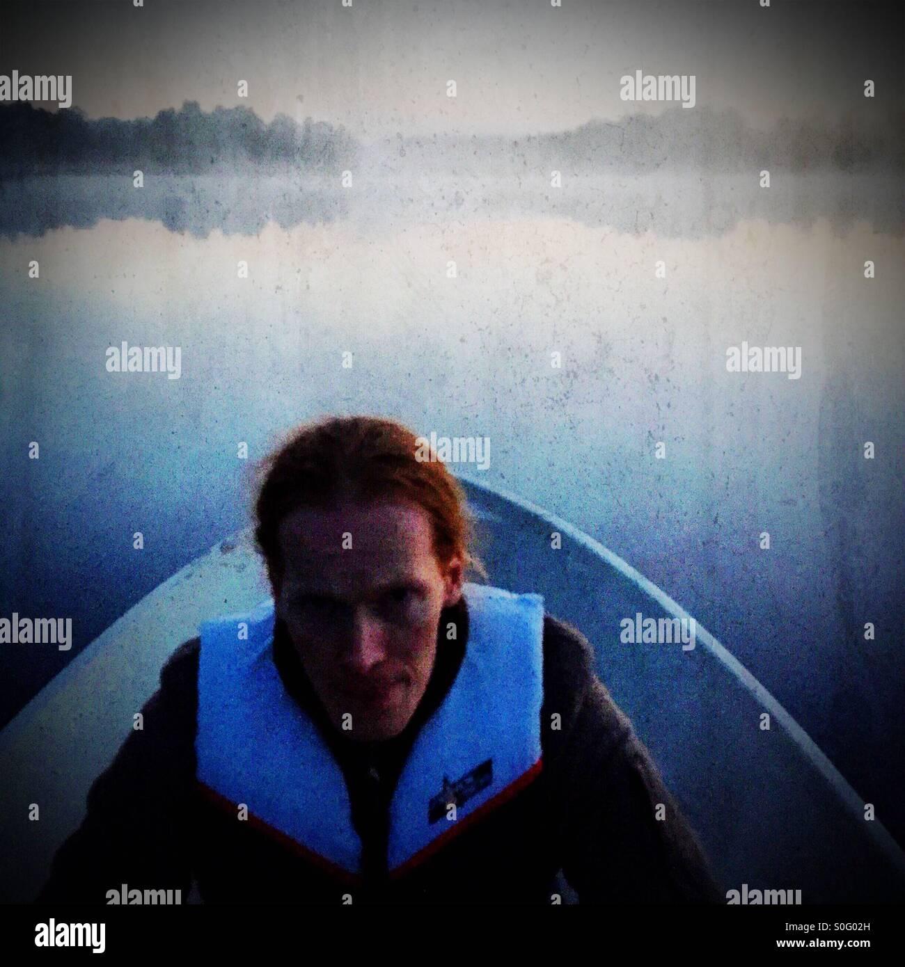 Una red headed hombre remando un bote Imagen De Stock