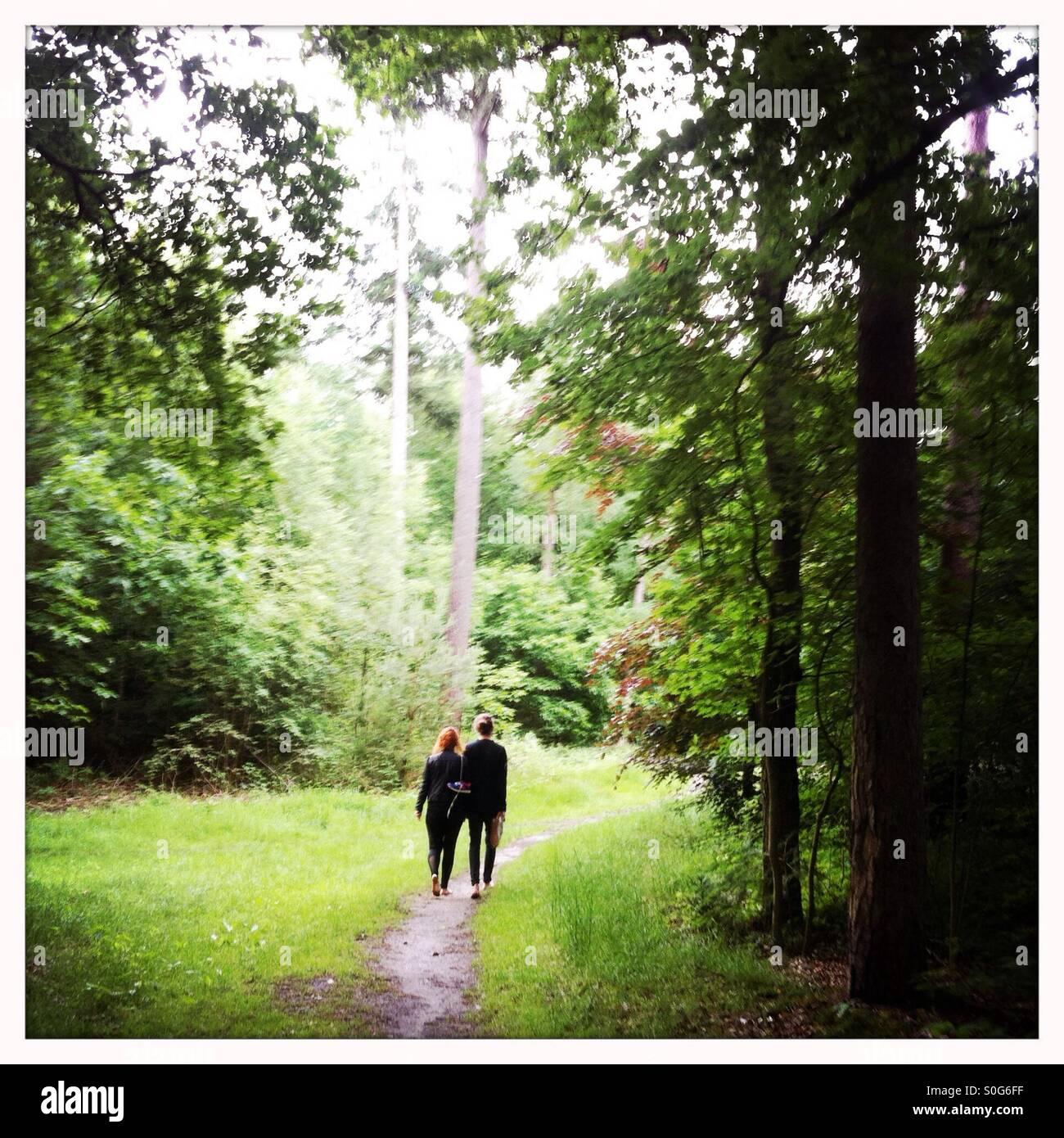 Chico y chica caminando juntos en un bosque en los pies descalzos Imagen De Stock