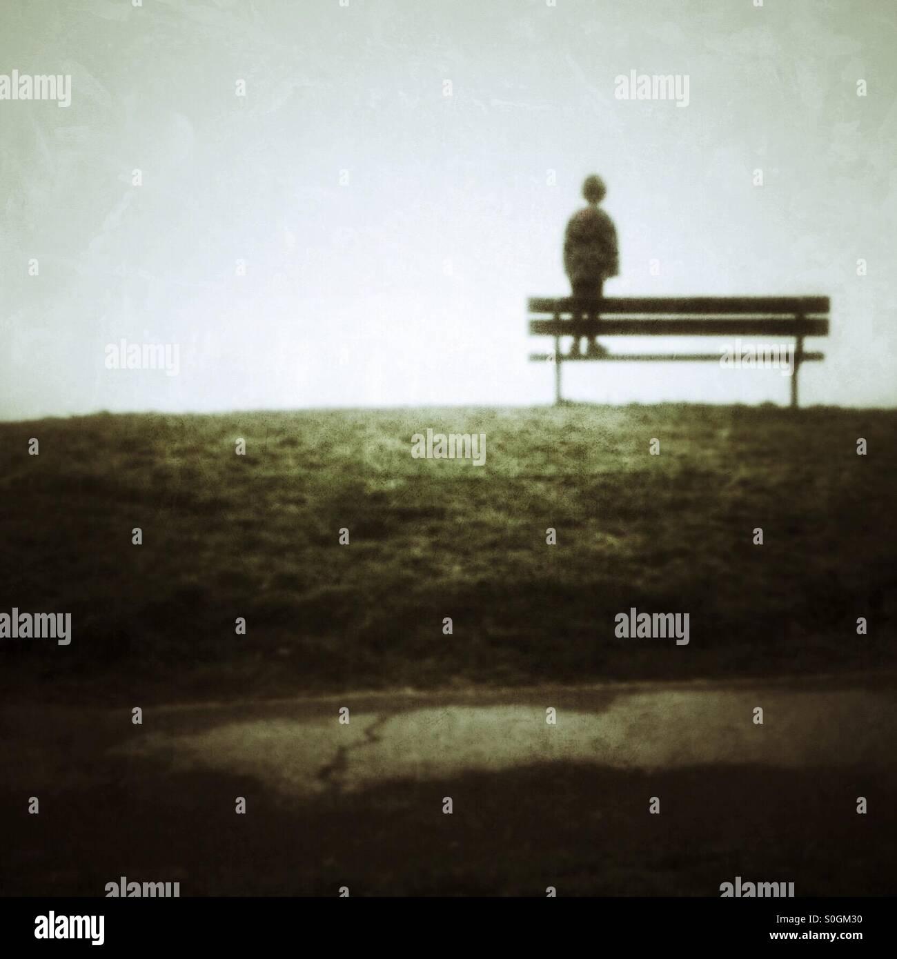 Niño esperando de pie en un banco del parque Imagen De Stock
