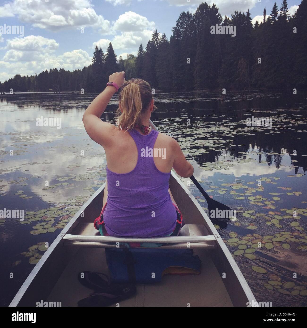 Chica remando en una canoa en un lago en el parque Algonquin, Ontario, Canadá Imagen De Stock