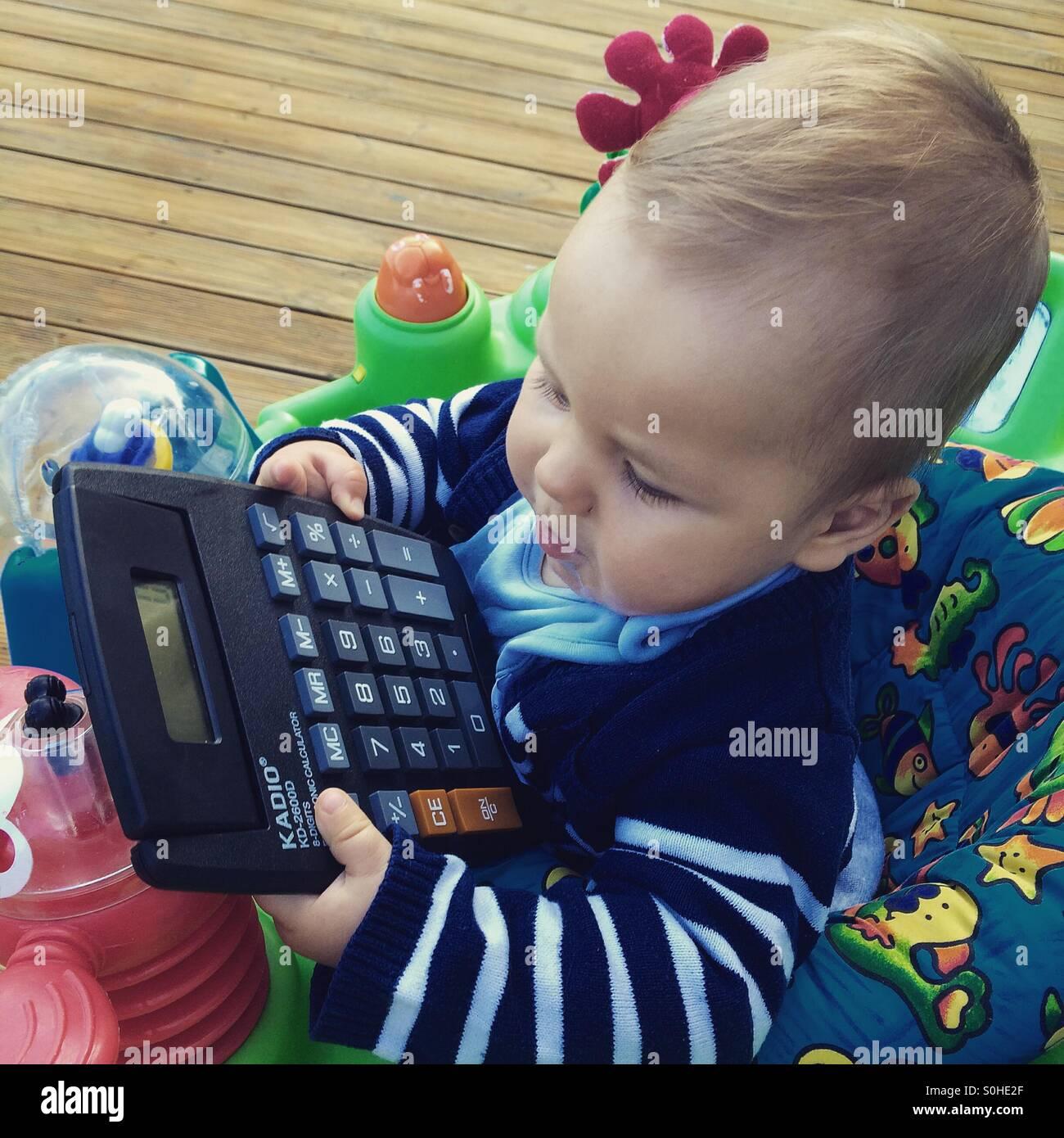 Baby Boy jugando con la calculadora Foto de stock