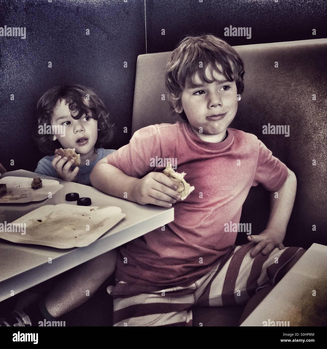 Los muchachos de comer bocadillos en la cafetería Imagen De Stock