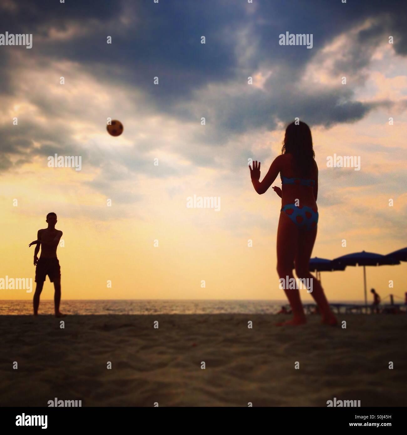 Chico y chica jugando con una pelota en la playa Imagen De Stock