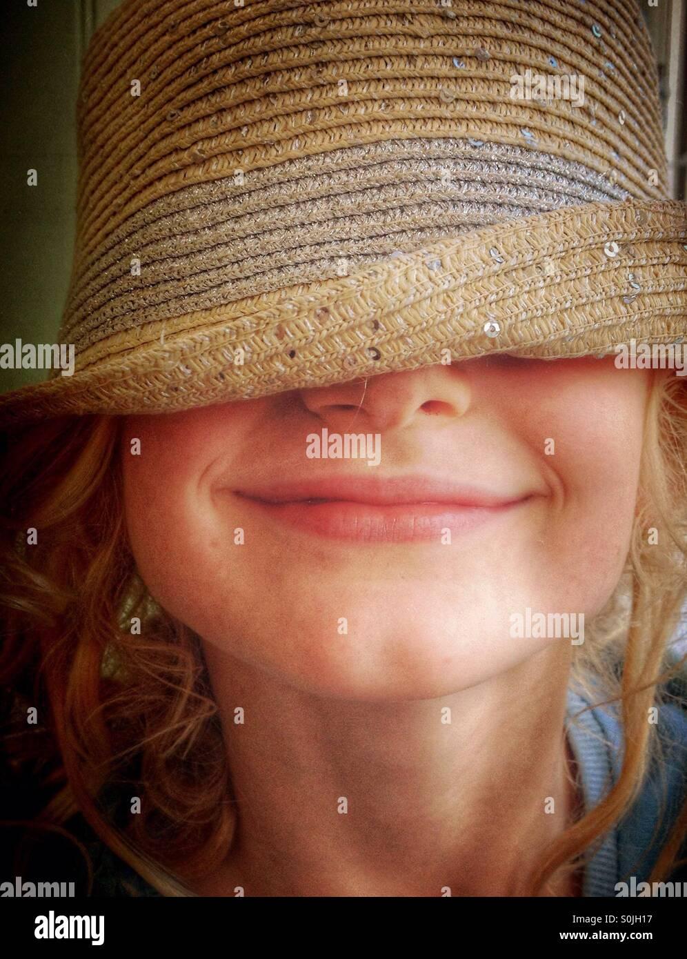 Niña vestidos de sombrero sobre sus ojos y sonriendo Imagen De Stock