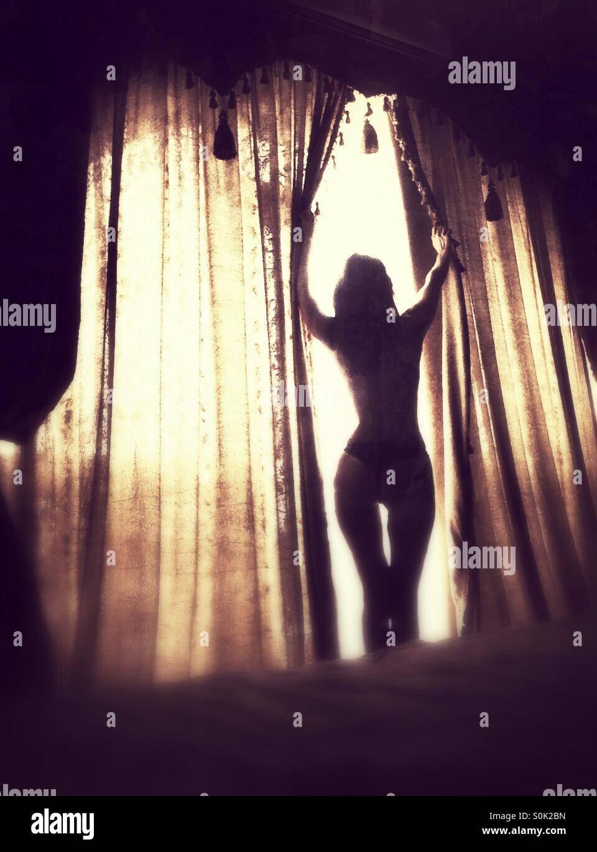 Chica abrir las persianas de la ventana en la mañana Imagen De Stock