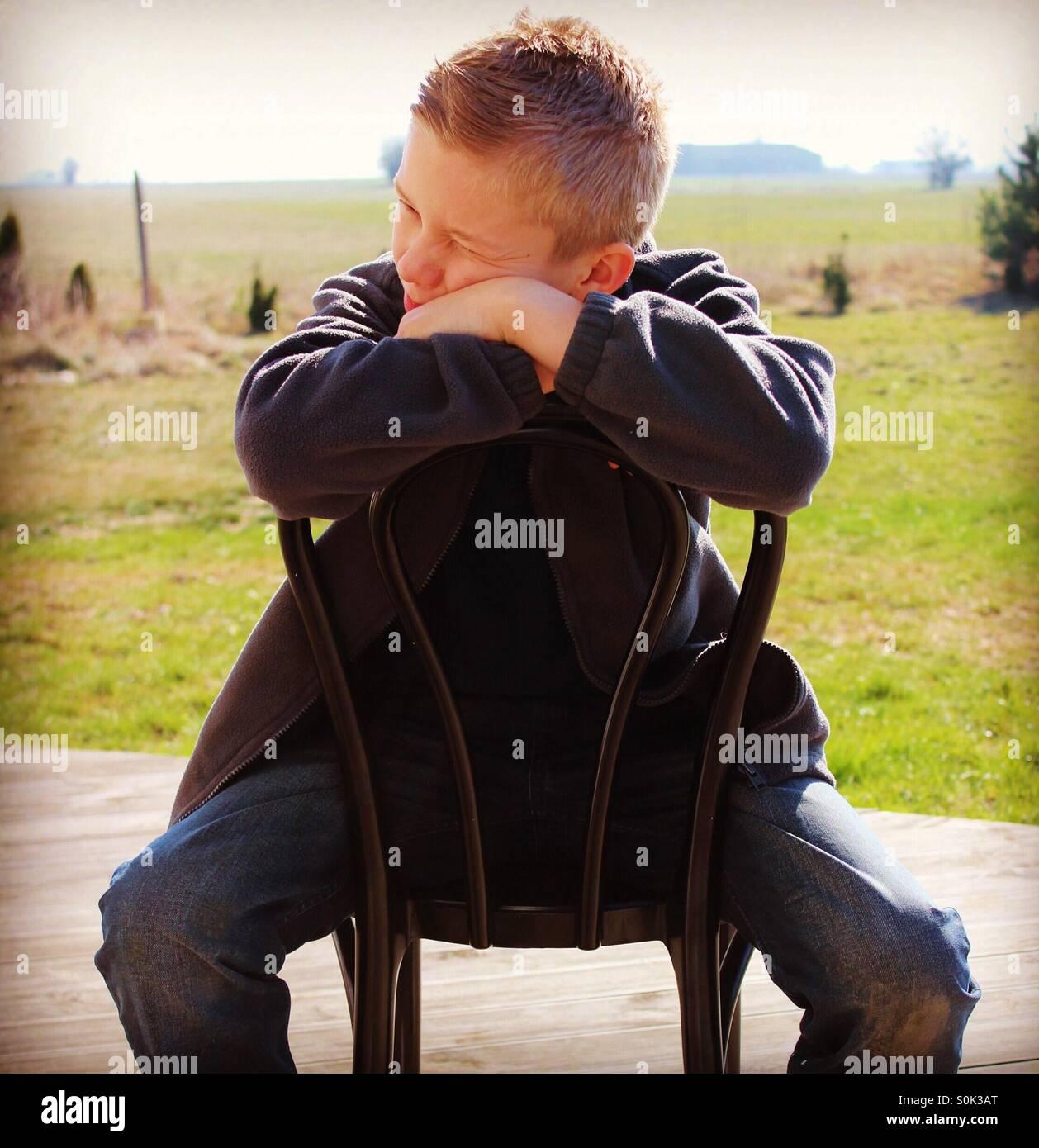 Adolescente sentado al revés en una silla negra fuera en el porche de atrás , deck de madera , buscando lateralmente Foto de stock