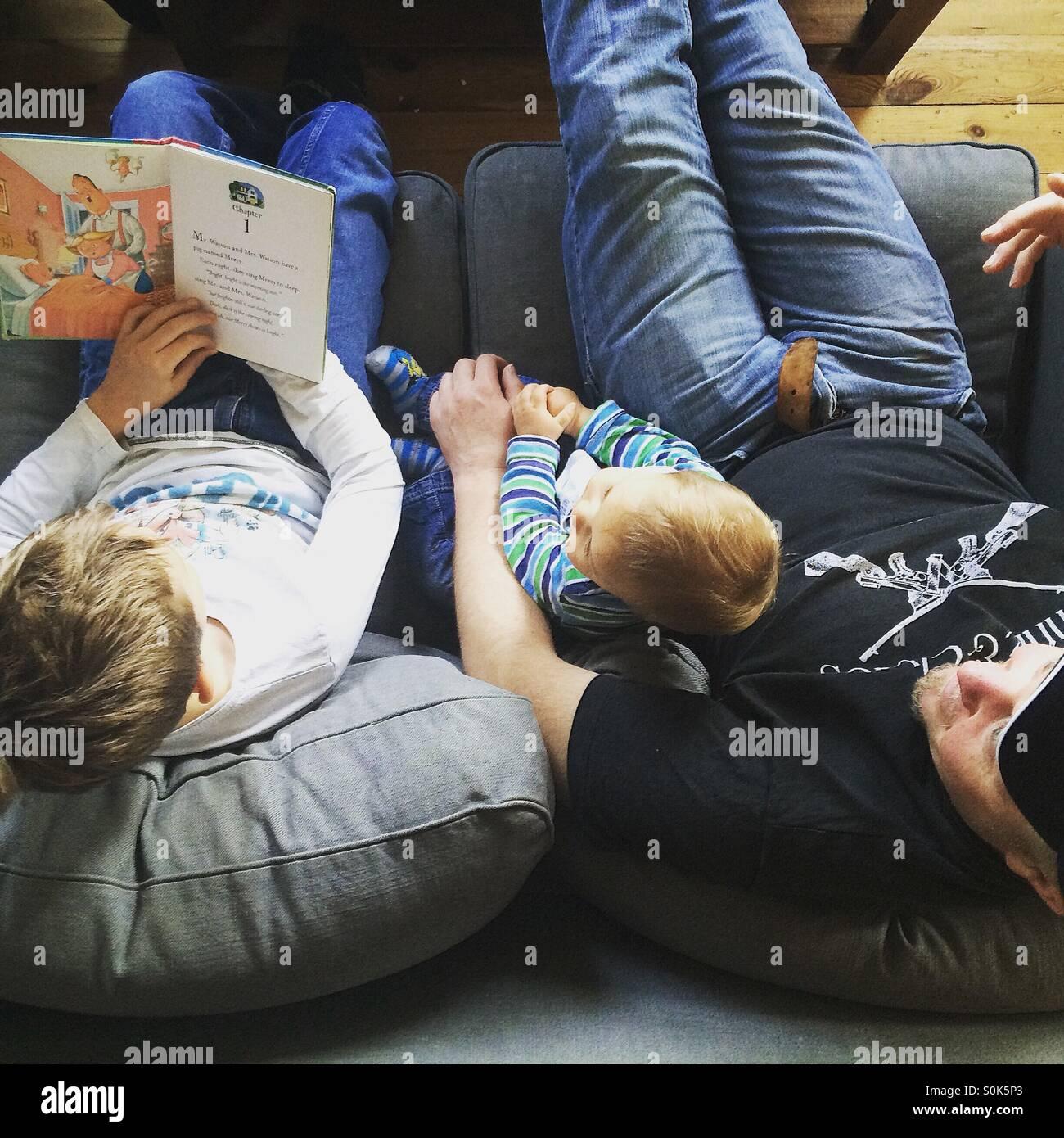 La foto de arriba de un padre con sus dos hijos , de los cuales está leyendo un libro en voz alta a su hermano Imagen De Stock