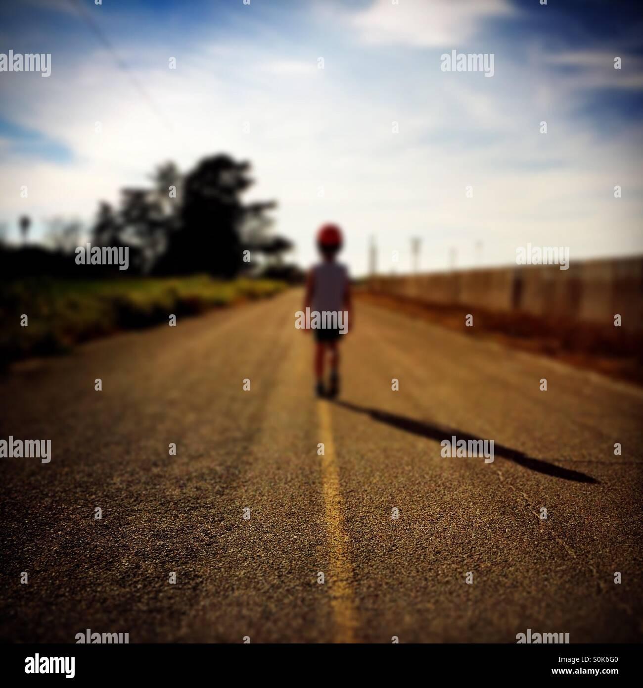 Un niño de 7 años se encuentra en medio de una carretera rural llevando su casco de bicicleta. Imagen De Stock