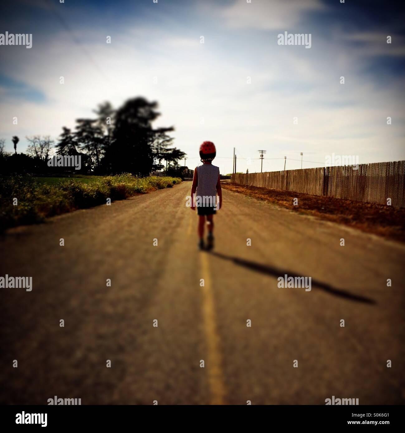Un niño de 7 años camina por medio de una carretera rural llevando su casco de bicicleta. Imagen De Stock