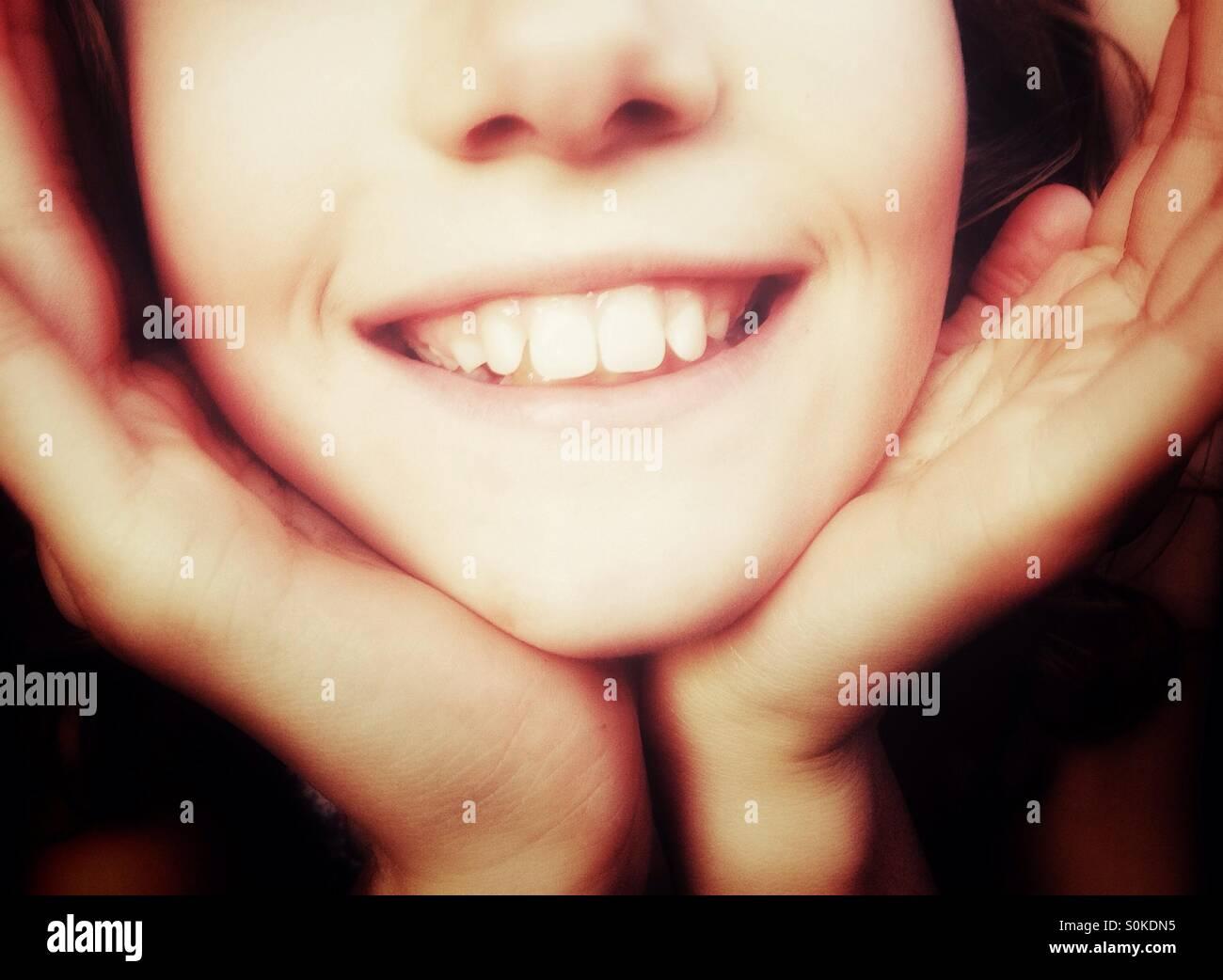 Cerca de chica sonriente con cara acopado en sus manos Imagen De Stock