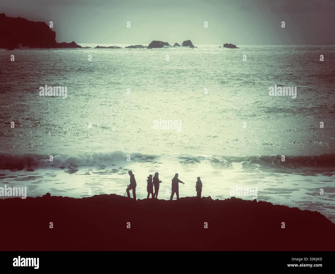 Cinco personas siluetas contra un mar con olas. Imagen De Stock