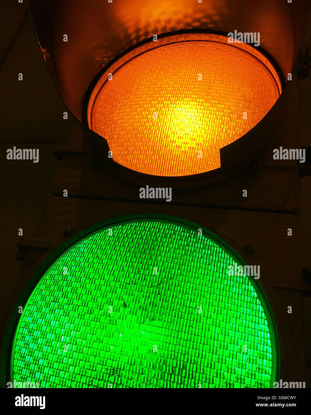 Close-up de iluminado en ámbar amarillo y verde y las señales de tráfico. Imagen De Stock