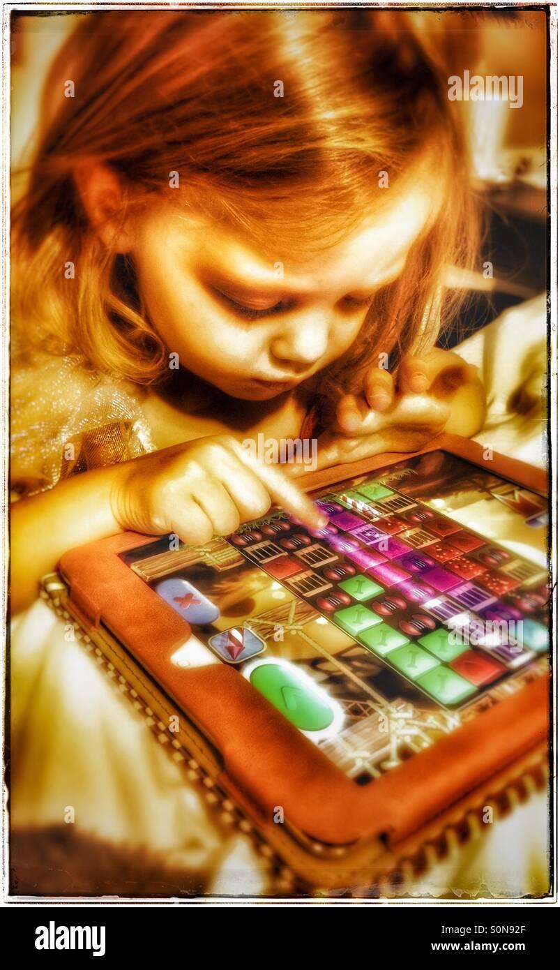 Niña jugando saga Pet Rescue en un iPad Foto de stock