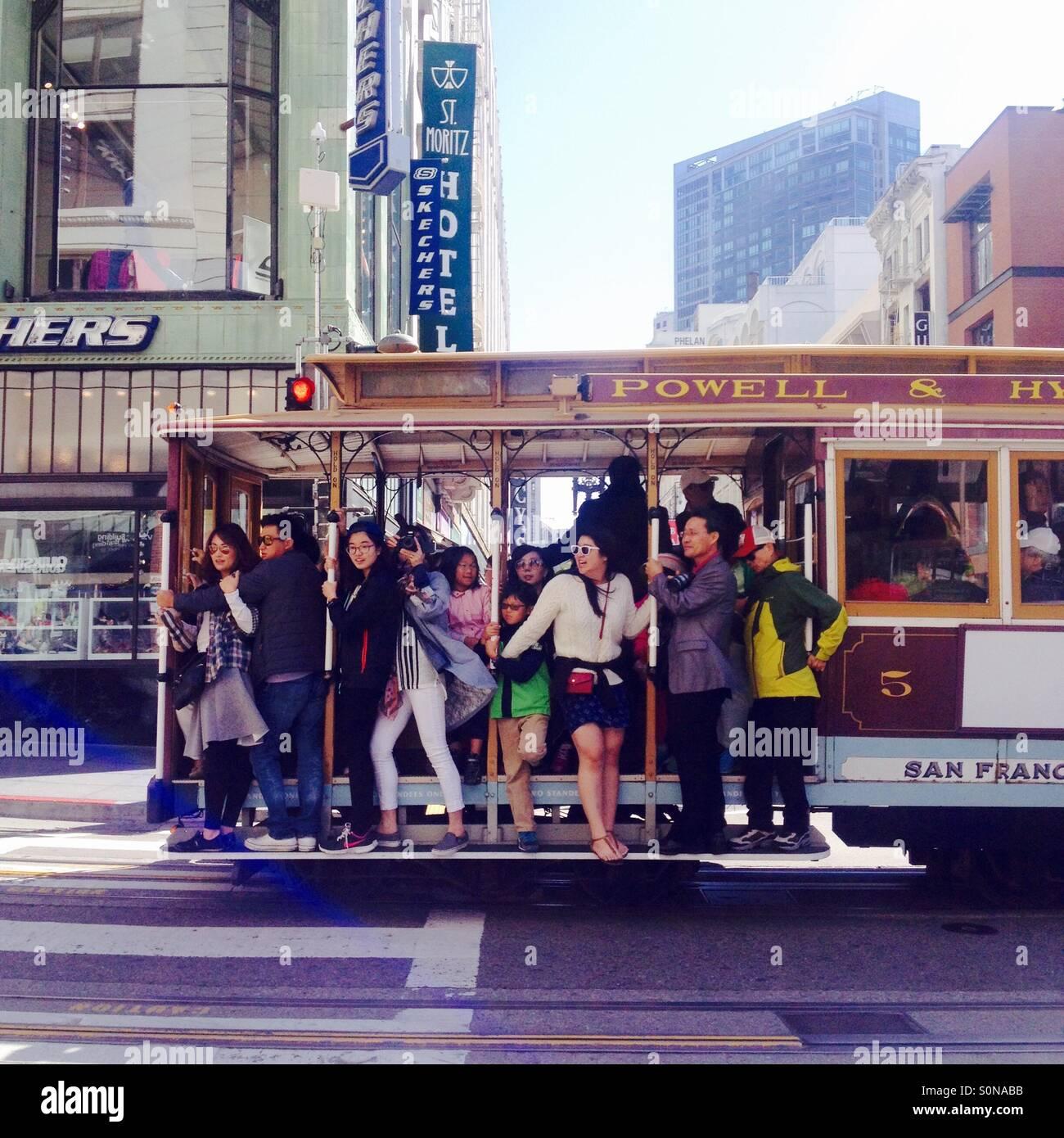 Los turistas montar un teleférico en el centro de San Francisco. Imagen De Stock