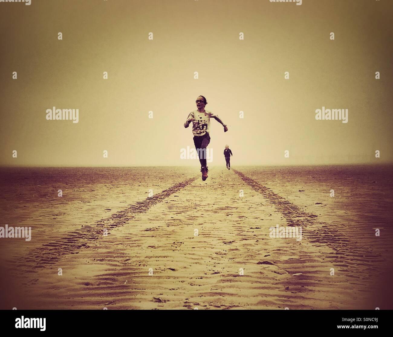 Dos jóvenes chicas que se divierten corriendo en playa desierta entre las huellas de los neumáticos Imagen De Stock